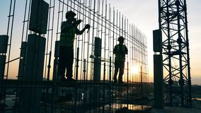 Sunset building lot with engineers making a metal carcass. 4K stock footage
