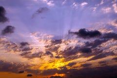Sunset burst. Dramatic Sunbeam through clouds blue and orange twilight sky Royalty Free Stock Photos