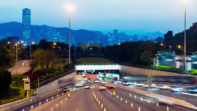 Sunset Busy Traffic Going Into Tunnel. Zoom Out Shot. Hong Kong rush hour sunset timelapse. Commercial Office Buildings with commercial billboards. Busy cars stock footage