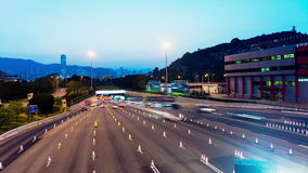 Sunset Busy Traffic Going Into Tunnel. Zoom In Shot. Hong Kong rush hour sunset timelapse. Commercial Office Buildings with commercial billboards. Busy cars stock video footage
