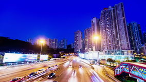 Sunset Busy Traffic. Wide Tilt Down Shot. Hong Kong rush hour sunset timelapse. Residential buildings at the back. Commercial billboards at both sides of the stock video footage