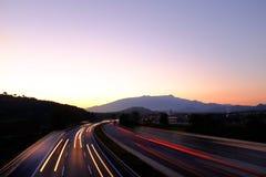 Sunset on buzy highway Stock Photo