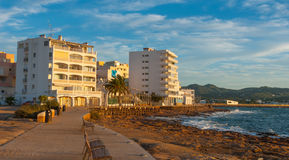 Sunset on the Cafes on Ibiza beaches. Golden glow as the sun goes down in St Antoni de Portmany Balearic Islands, Spain. People sit on bleacher benches & watch stock images