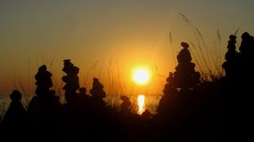 Spiritual Sunset with Cairns on the Ocean royalty free stock image