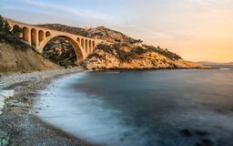 Sunset at Calanque des Eaux Salees or Salt water rocky inlet with Pebble beach and old railway bridge near Marseille France