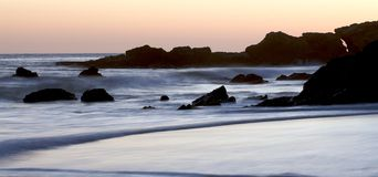 Sunset on California Beach rocks and cliffs Royalty Free Stock Photography