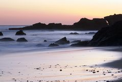 Sunset on California Beach rocks and cliffs Royalty Free Stock Images