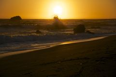 Sunset on the California Coast. A wave crashes on the rocks off shore at Jenner, California as the sun sets through the foggy marine layer Stock Image