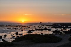 Sunset at the californian coast. Showing a nice silhouette of rocks at the beach and a lighthouse in the background stock photography