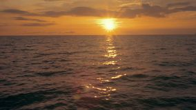 Sunset on a calm and peaceful ocean. Establishing shot of an ocean at sunset. 4K UHD footage with high dynamic range stock video