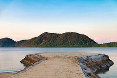Sunset on the calm Thai beach with pier for boats Royalty Free Stock Photos