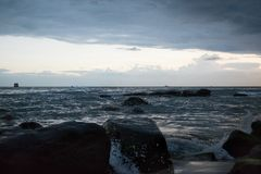 Sunset in Cambodia at the seaside. Sea waves roll on sands and rocks. stock image