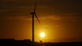 Sunset in Canary Islands. Car under wind energy tower at sunset Royalty Free Stock Images