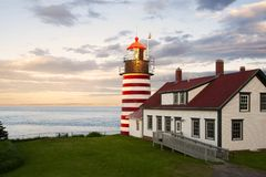 "Sunset by Candy Cane Lighthouse in New England. Sunset by West Quoddy Head lighthouse, with its red and white stripes, referred to as the ""candy cane stock photos"