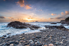 Sunset at Cape Cornwall. Waves crashing over rocks at Priest's Cove on the rugged Cornish coastline at cape Cornwall royalty free stock images