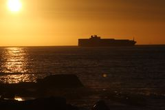 Sunset at capetown beach ships in backround. Sun reflects in water royalty free stock images