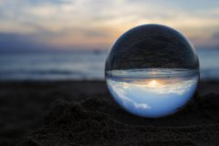 Sunset Captured in Glass or Crystal Ball on Beach. Sunset sky with ocean and beach captured in glass ball royalty free stock photography