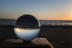 Sunset captured in glass crystal sphere. Sunset on the beach on wooden pole captured in glass crystal sphere royalty free stock image