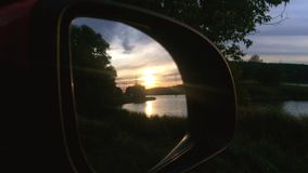 Sunset in car mirror. Forest and lake. Action in real time stock video
