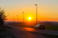 Sunset with a car passing by Royalty Free Stock Photography