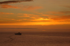 Sunset and cargo ship Stock Image