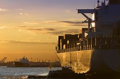 Sunset Cargo-Ship. Golden sun beams lighten a cargo-ship in Manhattan Bay Stock Photos
