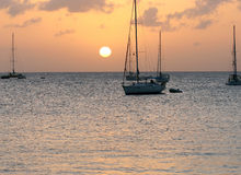 Sunset on Caribbean bay. Boats floating in bay near St. Lucia island watching sunset Royalty Free Stock Photo