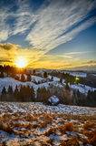 Sunset in Carpathian mountains. Colorful landscape with bright blue sky and sun in winter, view on a valley with snow and dry yellow grass Stock Photos