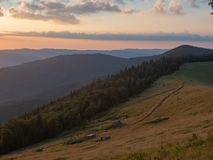 Sunset in Carpathians mountains in august, west Ukraine. Landscape of mountain pasture, hillsides covered with dense. Forest and evening sky with clouds royalty free stock photography