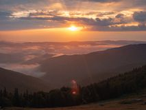 Sunset in Carpathians mountains, west Ukraine. The sun illuminating evening sky with clouds. Hillsides covered with. Green dense forest. Ukrainian nature stock image