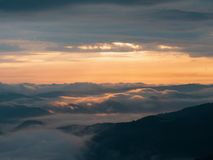 Sunset in Carpathians at summer, west Ukraine. The sun covered with high dense clouds. Low clouds flowing over mountain. Peaks. Landscape of Ukrainian nature in stock images