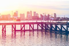 Sunset casting a pink light on a disused jetty in London with an. Sunset casting a pink light on a disused jetty adjacent to the Thames Barrier in London with an Royalty Free Stock Images