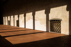 The sunset casts the shadows from the colonnade onto the gallery with windows seized with steel bars and a flor of brown tiles Stock Photos