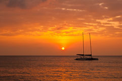 Sunset with Catamaran boat. Sunset background with Catamaran boat silhouette Royalty Free Stock Photography