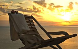 Sunset. chaise lounge with a towel and sunglasses stock photography