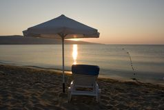 Sunset, Chaise and Umbrella. Sunset or Sunrise in horizon with a sandy beach, chaise lounge and umbrella in foreground. Chair is facing outward toward the ocean stock image