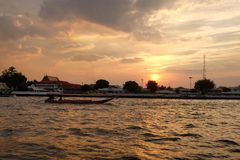 Sunset at Chao Phraya River. Sky colors warmth waterfront boat sun shadows backlit contrast Stock Photo