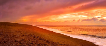 Sunset on Chesil Beach. A calm, balmy sunset at the Chesil Beach. The bright orange, sky reflecting in the water Stock Image