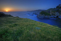 Sunset on China Cove, Point Lobos. The sun sets on the rugged Pacifc coast on a grassy knoll above China Cove in Point Lobos State Preserve in Carmel, California stock image