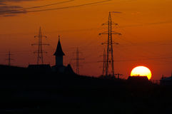 Sunset, church tower and electrical poles Royalty Free Stock Photography