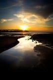 Sunset on a city beach Stock Photos