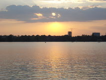 Sunset on city lake, with silhouette of building under construction in the background Stock Photos