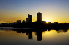 Sunset in the city, reflcting in smooth water Royalty Free Stock Images