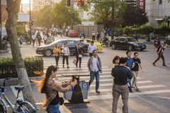 Sunset city scenery, pedestrians, traffic flow. Royalty Free Stock Images