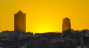 Sunset in the city, silhouettes of two multi-storey houses against the background of crimson sky Stock Photography