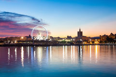 Sunset cityscape with ferris wheel in motion. Malaga city, Spain Royalty Free Stock Image