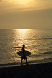 Sunset Clearwater Beach. Surfer walking along beach at sunset Royalty Free Stock Image