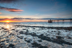 Sunset at Clevedon Pier. Dramatic sunset on the beach at Clevedon on the Somerset coast stock photography