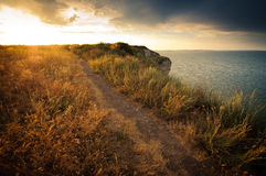 Sunset on the cliff near a lake Stock Images