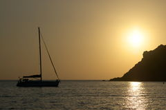 Sunset with cliff and yacht Royalty Free Stock Image